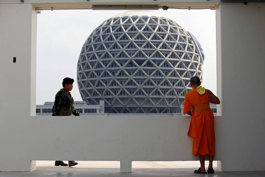 Soldado caminha próximo a monge budista no templo de Wat Phra Dhammakaya, na Tailândia - 10/03/2017