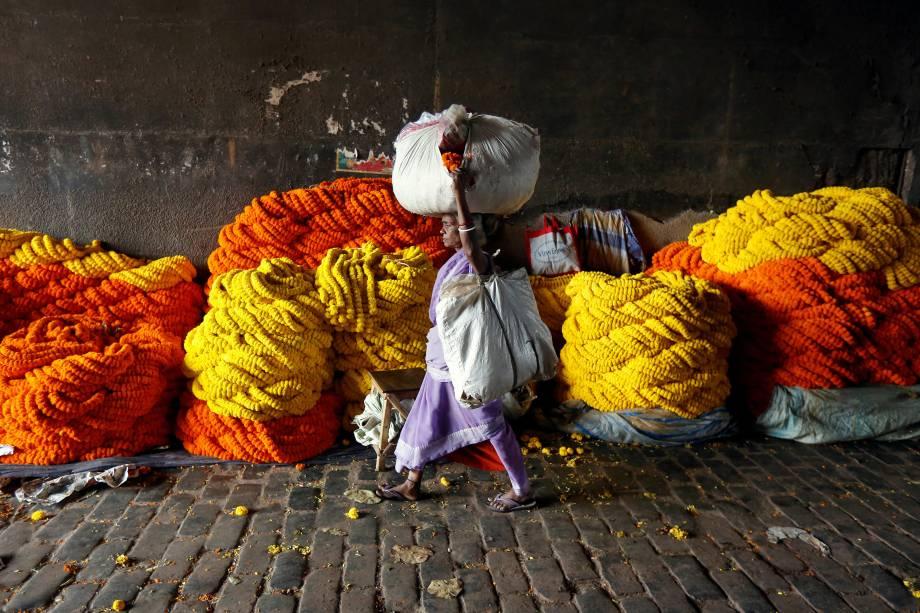 Mulher carrega flores em um mercado por atacado em Calcutá, na Índia - 20/03/2017