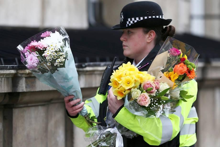 Policial carrega buquês de flores em Whitehall na manhã seguinte ao ataque em Londres - 23/03/2017