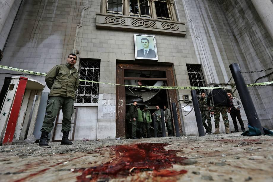 Forças de segurança sírias se reúnem sob um retrato do presidente Bashar Assad no antigo palácio de justiça em Damasco, após um atentado suicida - 15/03/2017