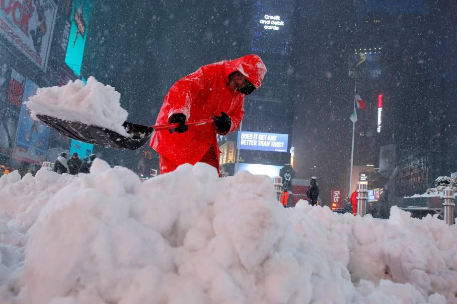 Trabalhador retira a neve da via em Times Square durante forte nevasca em Nova York - 14/03/2017