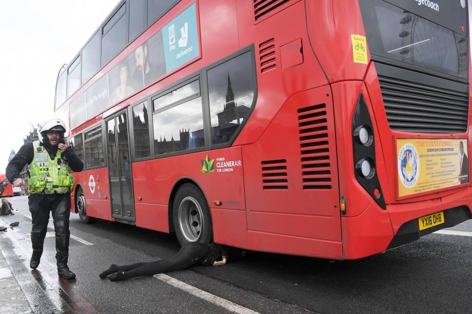 Mulher fica debaixo de um ônibus após incidente com tiros no Parlamento inglês na ponte de Westminster em Londres - 22/03/2017