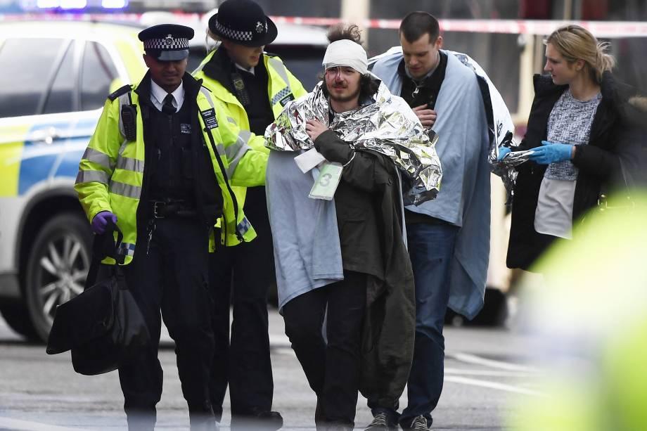 Homem ferido recebe atendimento após incidente com tiros nos arredores do Parlamento, na ponte de Westminster em Londres - 22/03/2017