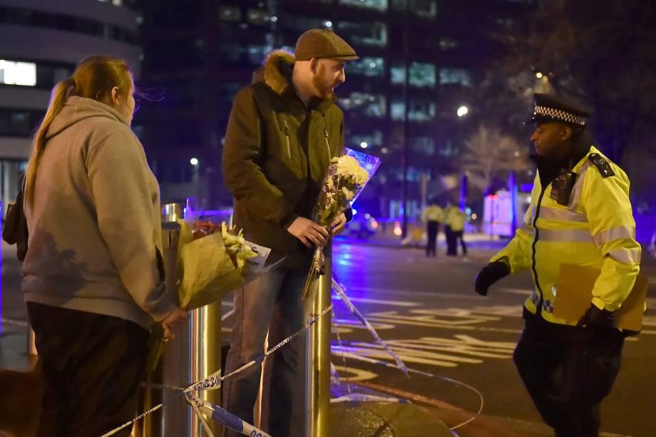 Pessoas deixam flores nos arredores do Parlamento em Londres após incidente com tiros - 22/03/2017
