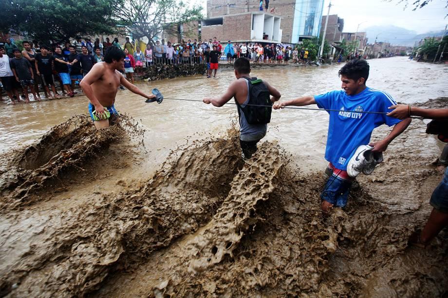 Moradores usam uma corda para atravessarem uma rua inundada na cidade de Trujillo, no Peru - 21/03/2017