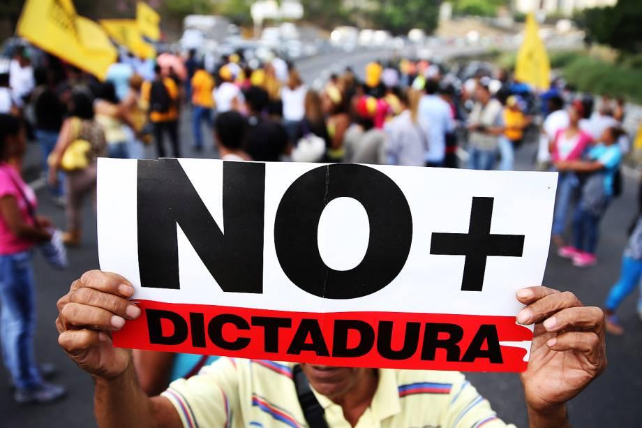 Manifestante segura cartaz com a mensagem 'Não mais ditadura' em protesto contra o presidente Nicolas Maduro, em uma rodovia de Caracas - 31/03/2017