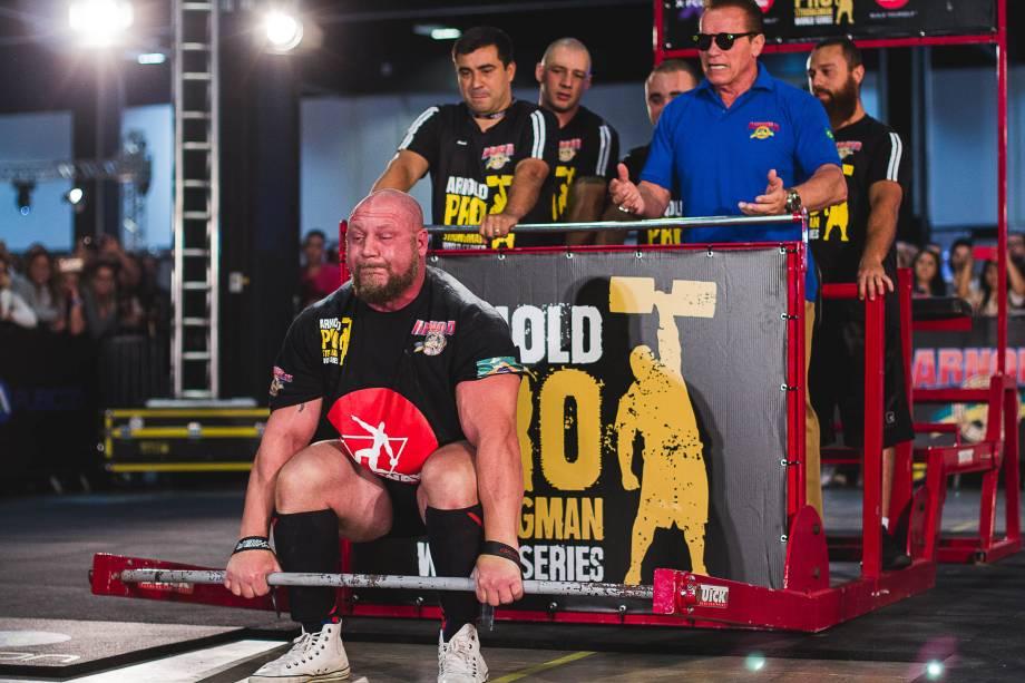 O brasileiro Marcos Ferrari participa de desafio de força para erguer aparelho com Arnold Schwarzenegger