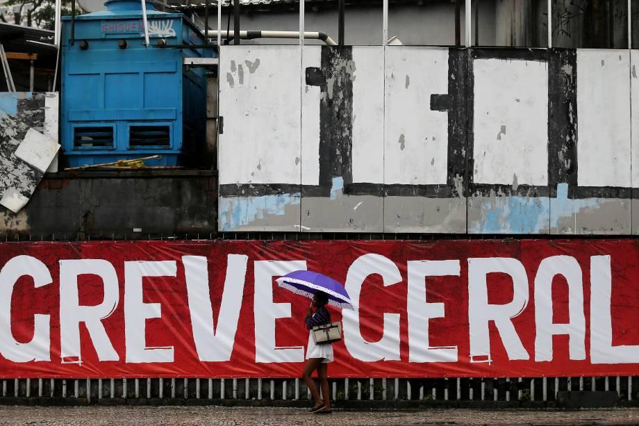 Mulher passa por uma faixa escrita 'Greve Geral' durante dia de manifestações contrárias às reformas propostas pelo governo Michel Temer no Rio de Janeiro - 28/04/2017