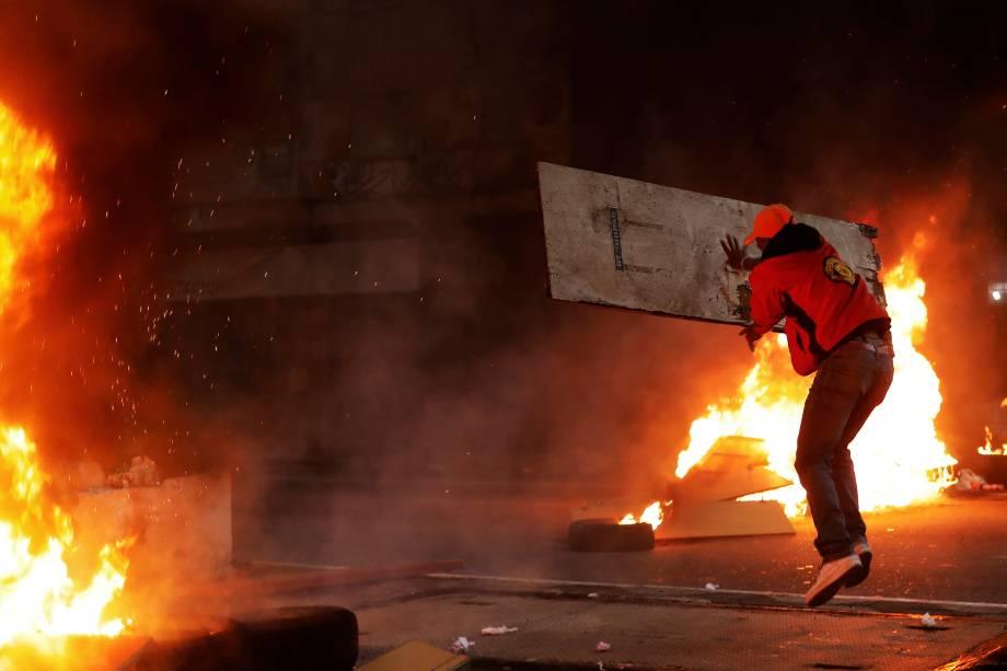 Integrante do Movimento dos Trabalhadores Sem-Teto lança um tábua de madeira sobre uma barricada em chamas durante protesto contra as reformas do governo Michel Temer em São Paulo - 28/04/2017