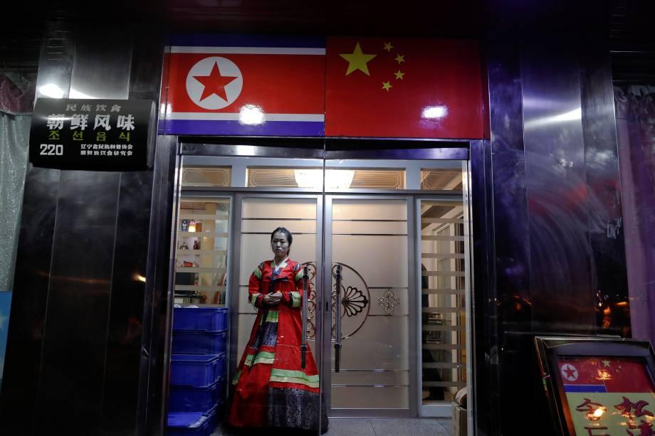 Mulher com vestimentas tradicionais convida pessoas a entrar em um restaurante de comida norte-coreana na cidade de Dandong, China - 30/03/2017