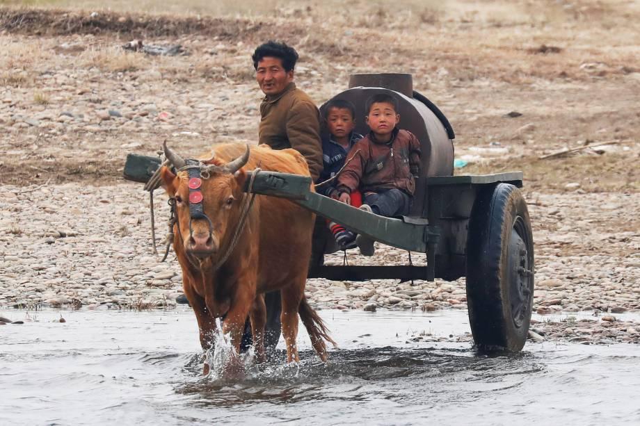 Homem e crianças passam por braço d'água próximo ao rio Yalu, no lado da Coreia do Norte, próximo a cidade de Sinuiju - 30/03/2017