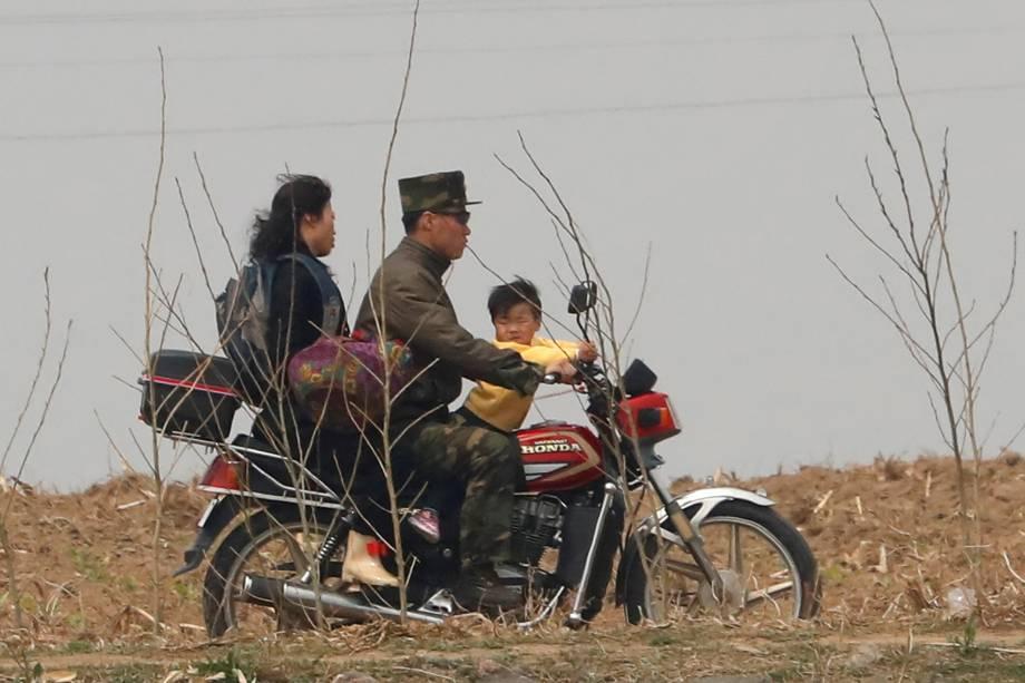 Soldado norte-coreano anda de moto com a família na fronteira com a China pelo rio Yalu, próximo a cidade de Sinuiju, na Coreia do Norte, e da província de Dandong, China  - 15/04/2017
