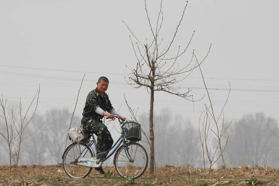 Soldado norte-coreano anda de bicicleta próximo ao rio Yalu, que faz fronteira com a China - 15/04/2017