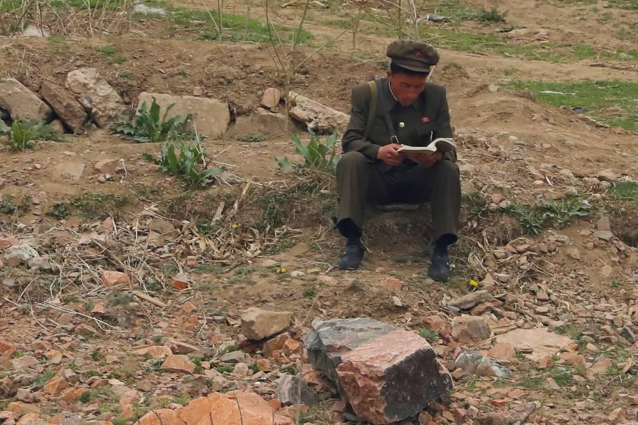 Soldado norte-coreano lê um livro próximo ao rio Yalu, que faz fronteira com a cidade próxima Dandong, na China, e com Sinuiju, na Coreia do Norte - 15/04/2017
