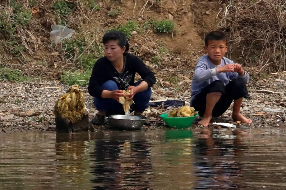 Norte-coreanos lavam alimentos no rio Yalu, que faz a fronteira de Dandong, na China, e de Sinuiju, Coreia do Norte - 16/04/2017