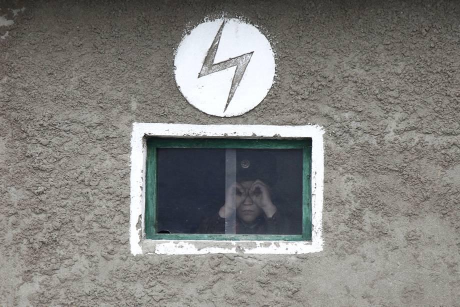 Soldado norte-coreano olha pela janela de uma torre de guarda do rio Yalu, que faz a fronteira entre China e Coreia do Norte -  16/04/2013