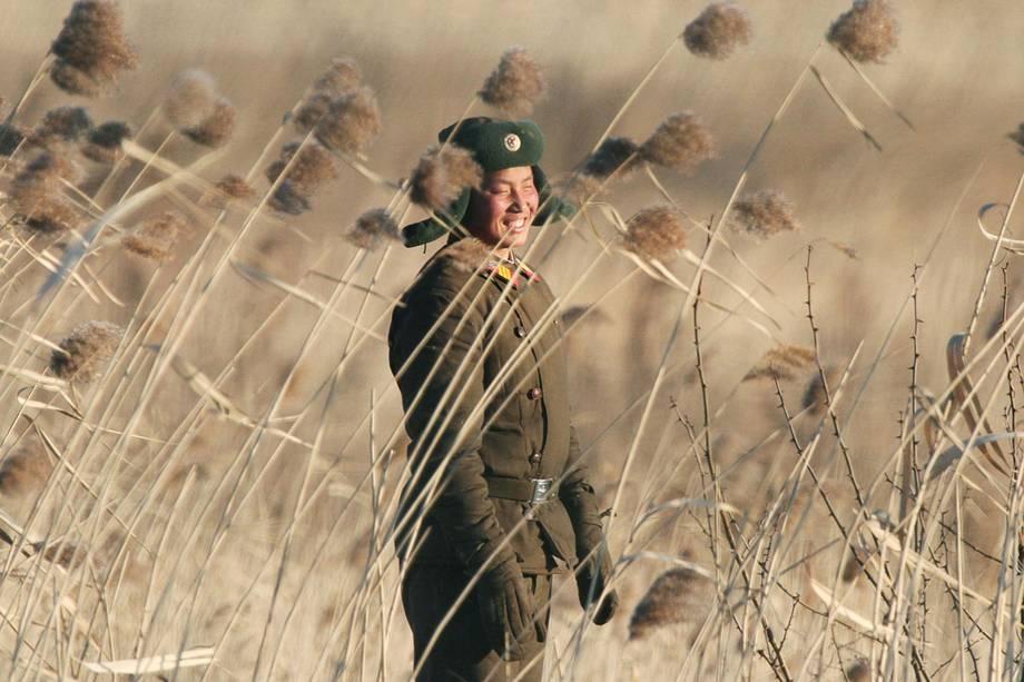 Soldado norte-coreano sorri próximo a cidade de Sinuiju, Coreia do Norte, visto do lado oposto na cidade de Dandong, China - 06/01/2016