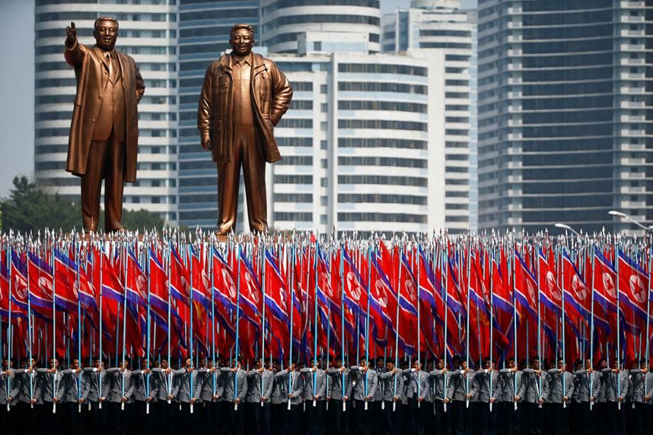 """Civis e militares comparecem ao festival do """"Dia do Sol"""", que marca o 105° aniversário de Kim Il Sung, ex-líder da Coreia do Norte, retratado na estátua da direita, e Kim Jong Il, na da esquerda - 17/04/2017"""