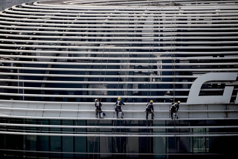 Trabalhadores limpam vidraça de prédio pelo lado de fora em Pequim, na China - 14/04/2017