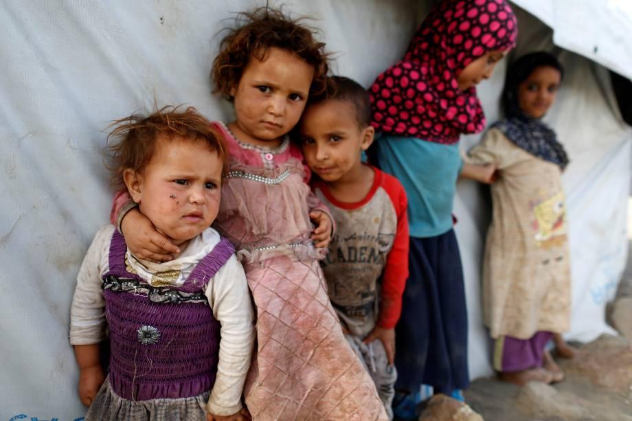 Crianças fotografados ao lado de uma barraca em um acampamento para pessoas deslocadas pela guerra perto de Sanaa, no Iêmen - 24/04/2017