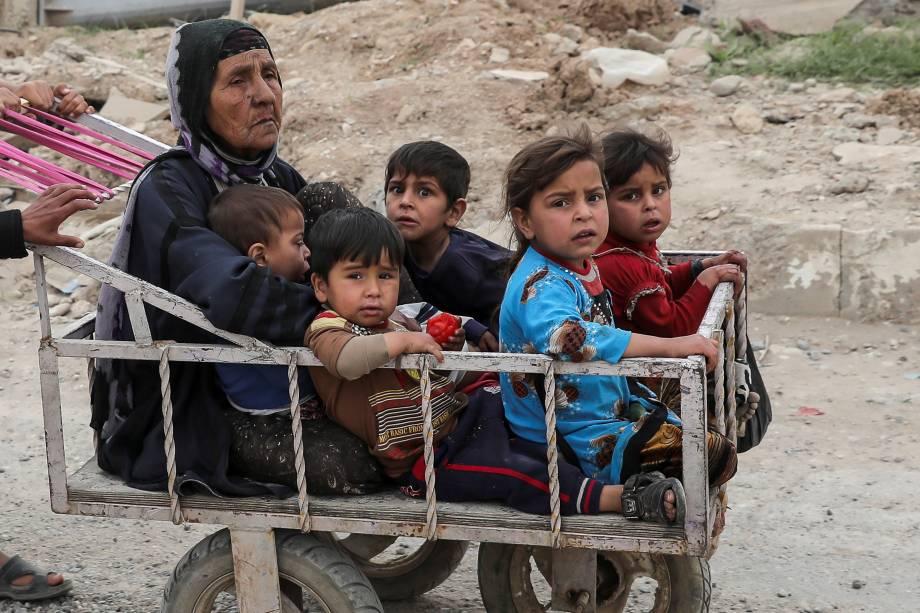Mulher e crianças deslocadas são transportados em carrinho na tentativa de fugir das áreas de conflito entre forças de segurança do Iraque e jihadistas do Estado Islâmico em Mosul - 24/04/2017