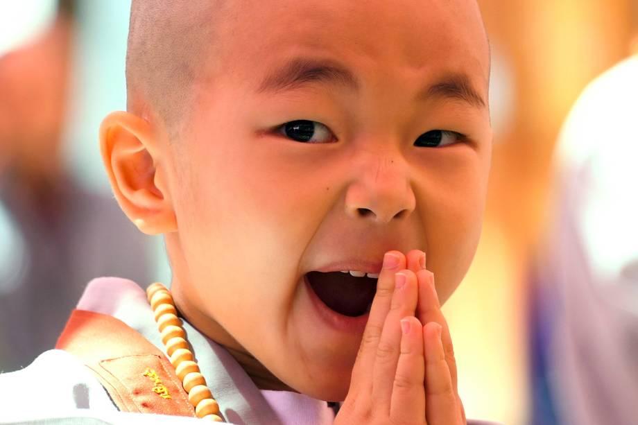 """Criança reage depois de ter sua cabeça raspada por monges budistas durante uma cerimônia intitulada """"Crianças tornando-se monges budistas"""", no templo Jogye em Seul, na Coreia do Sul - 19/04/2017"""