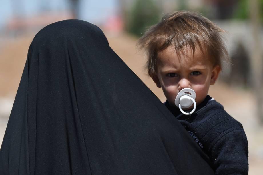 Mulher carrega uma criança em uma rua na parte ocidental da cidade de Mosul, norte do Iraque. Forças iraquianas continuam a ofensiva contra jihadistas do Estado Islâmico para retomada de territórios - 24/04/2017