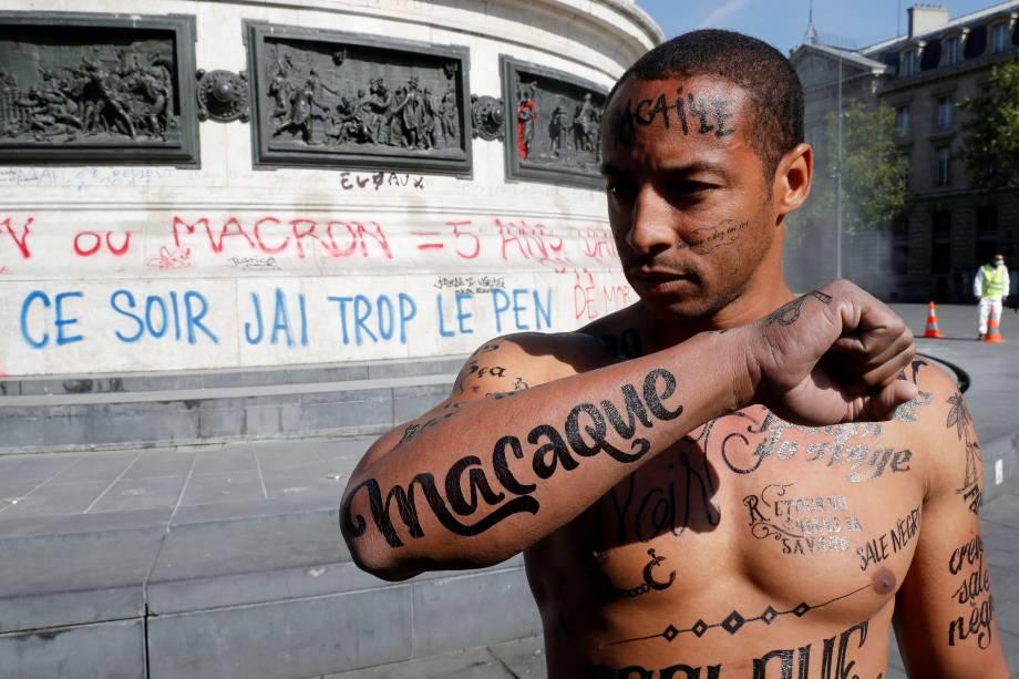 Homem com o corpo coberto de insultos racistas participa de um evento organizado pelo Conselho Representativo das Associações Negras da França (CRAN) para protestar contra o racismo, um dia após o primeiro turno das eleições presidenciais francesas no centro de Paris - 24/04/2017