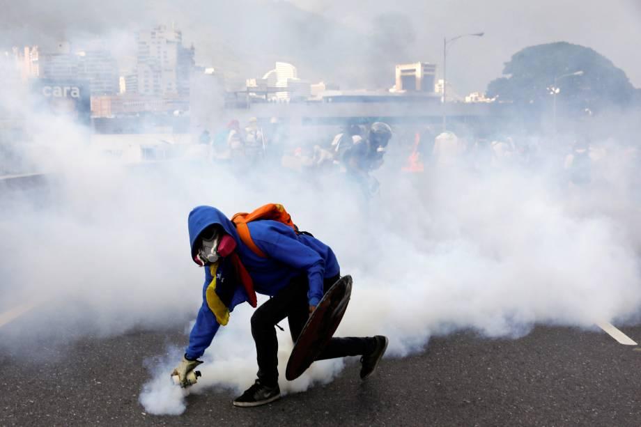 Manifestante joga uma granada de gás lacrimogêneo na polícia durante protesto contra o presidente da Venezuela, Nicolás Maduro, em Caracas - 24/04/2017