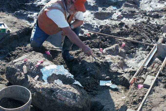 Paleontólogo Don Swanson apontando para um fragmento de rocha que, segundo o cientista, teria sido afiado por humanos