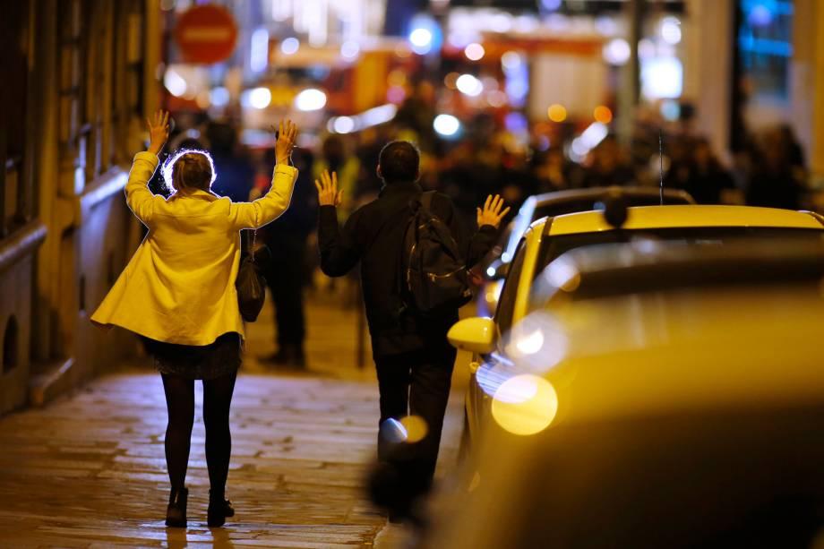 Mulheres levantam os braços para mostrar as mãos enquanto caminham em direção a polícia após tiroteio na  Champs Élysees, na França - 20/04/2017