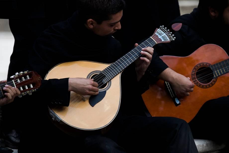 Estudante toca a viola de coimbra durante serenata em parque próximo à universidade de Coimbra