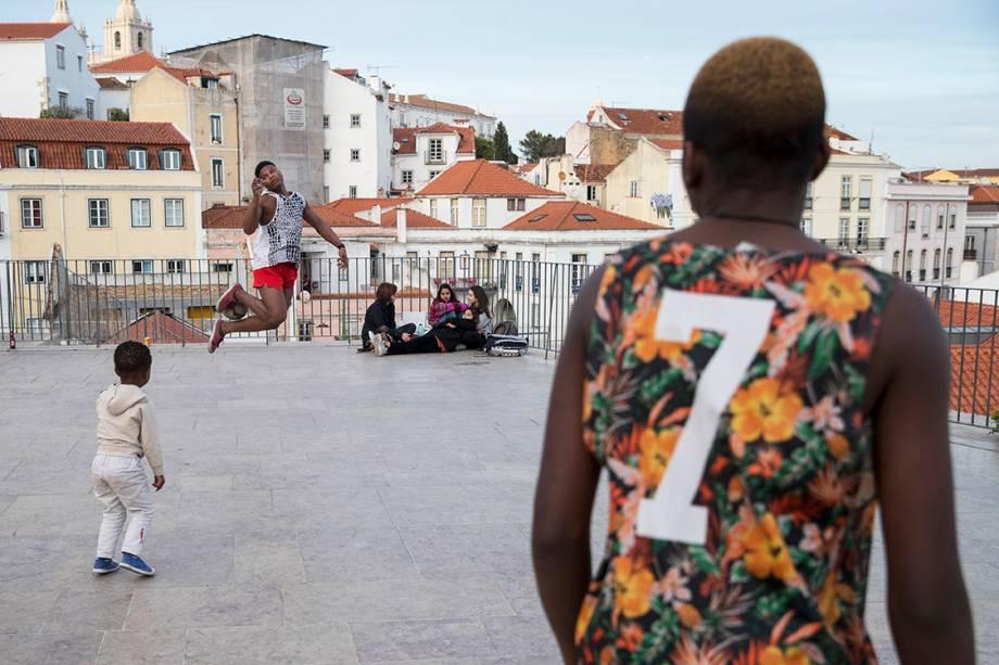 Rapazes jogam futebol no miradouro Portas do Sol, em Lisboa