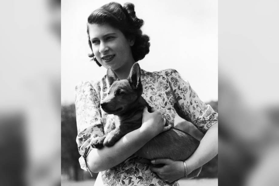 Princesa Elizabeth que segura Sue, um filhote de corgi, no castelo de Windsor em 1944