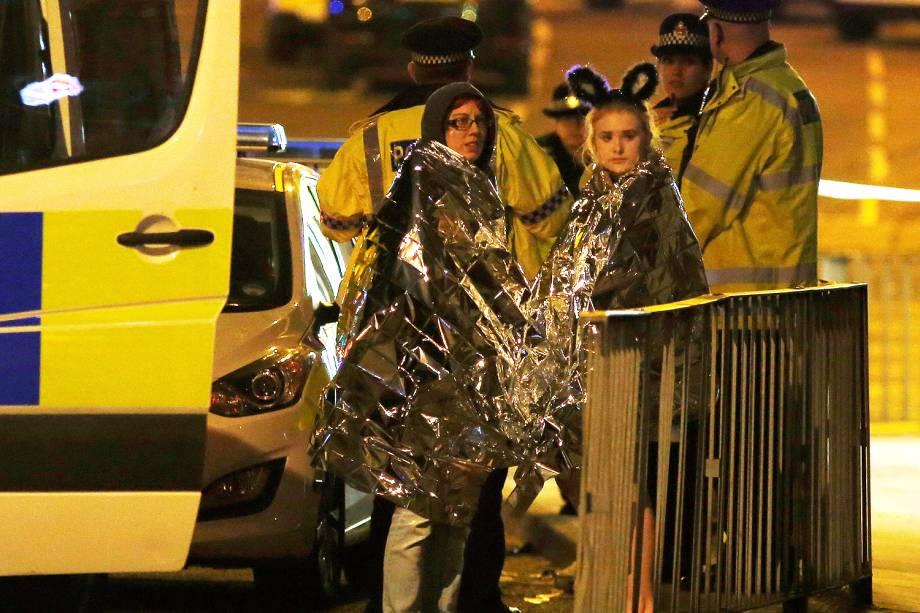 Fãs recebem assistência da polícia após explosão no show da cantora Ariana Grande que deixou ao menos 19 mortos e 50 feridos