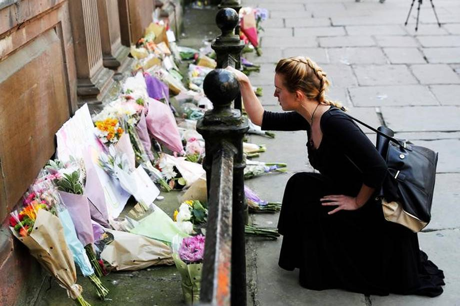 Mulher coloca flores para vítimas de ataque na Arena de Manchester, na Inglaterra -  23/05/2017