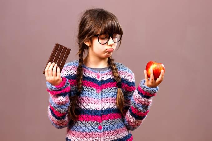 Menina em dúvida entre maça e barra de chocolate