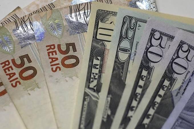 Dólar dos Estados Unidos ao lado de notas de real