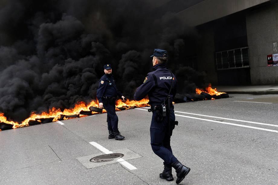 Policiais caminham em frente a uma barricada feita por manifestantes durante protestos do Dia do Trabalho em Gijón, Espanha