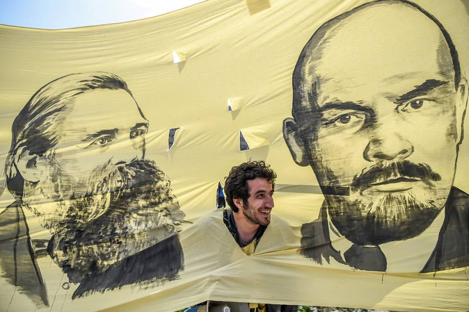 A man looks through the hole picturing German philosopher and communist thinker Friedrich Engels (L) and Soviet leader Vladimir Ilitch Lenin while he takes part in gather in Bakirkoy district as part of the the May Day rally, in Istanbul, on May 1, 2017. / AFP PHOTO / OZAN KOSE