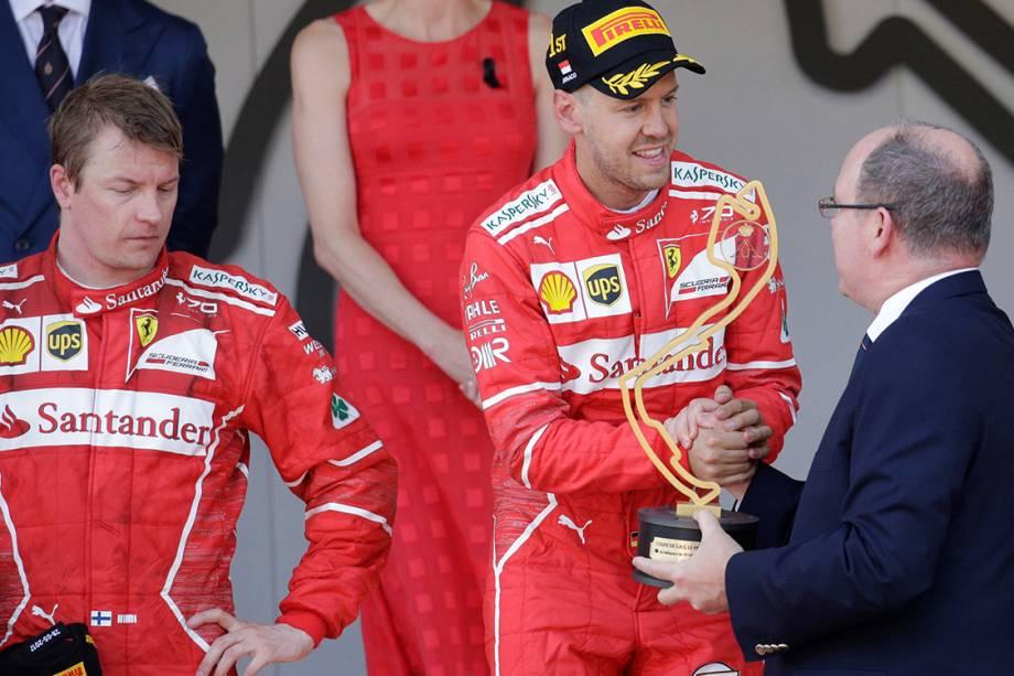 O piloto da Ferrari Sebastian Vettel recebe o troféu após superar o companheiro Kimi Raikkonen e vencer o GP de Mônaco