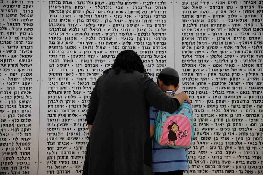 Uma mulher e um menino olham para um memorial em homenagem aos soldados mortos, em Israel