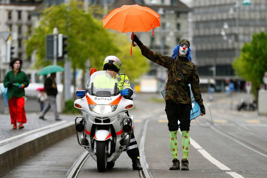 Manifestante vestido de palhaço segura um guarda-chuva sobre um policial, durante protesto do Dia do Trabalho em Zurique, Suíça