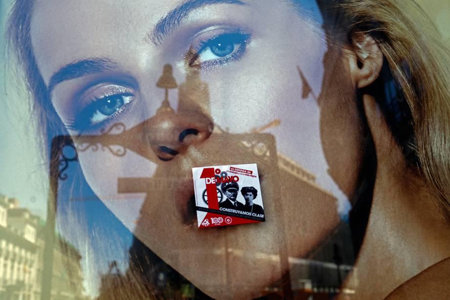 Um adesivo do Dia do Trabalho é colado sobre um cartaz durante protestos nesta segunda-feira (1) em Madri, Espanha