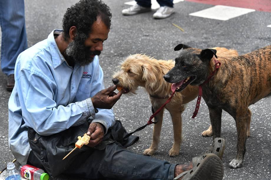 Morador de rua alimenta seus cães na Avenida Paulista, enquanto centrais sindicai fazem ato do Dia do Trabalho, em São Paulo