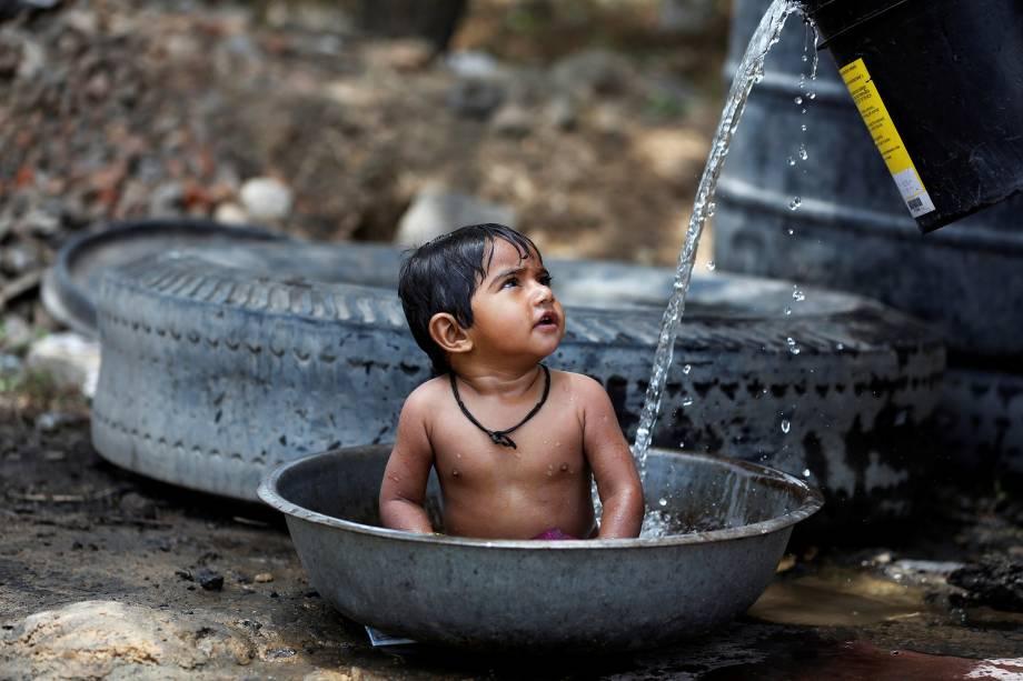 Menina se refresca em uma bacia com água em um dia quente em uma fazenda nos arredores de Ahmedabad, na Índia - 02/05/2017