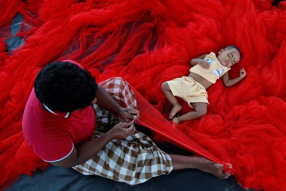 Pescador costura uma rede de pesca enquanto sua filha dorme ao seu lado  em uma praia no subúrbio de Kochi, na Índia - 23/05/2017