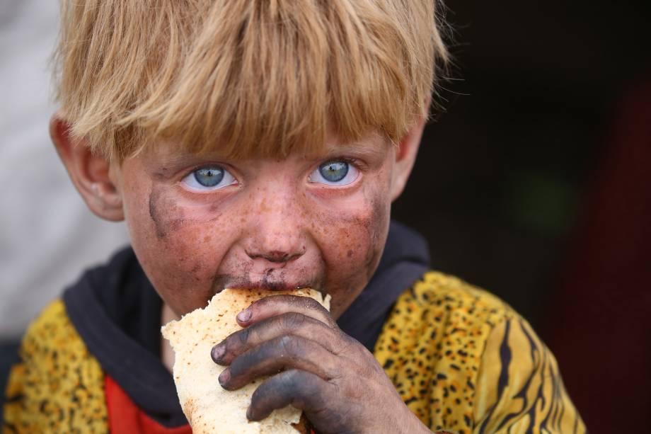 Criança refugiada se alimenta em um acampamento provisório na aldeia de AIn Issa, na Síria