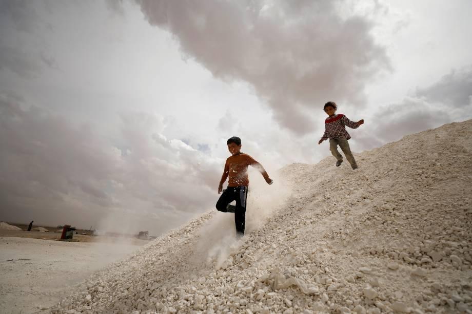 Crianças desabrigadas pelo conflito na cidade de Raqqa, brincam dentro de um acampamento provisório na aldeia de Ain Issa, na Síria