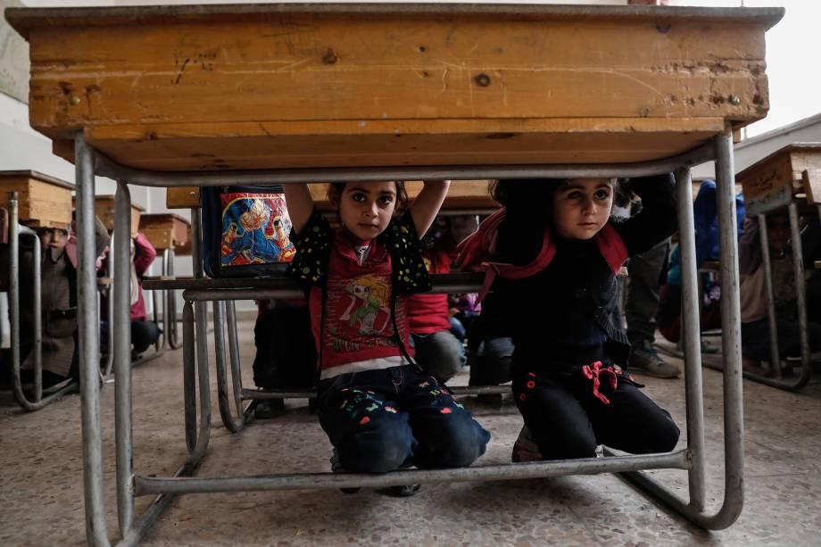 Alunos aprendem a se proteger de um bombardeio durante uma aula sobre segurança em guerra, conduzida por membros da defesa civil síria, na área de Harasta, controlada por rebeldes, nos arredores de Damasco - 02/05/2017